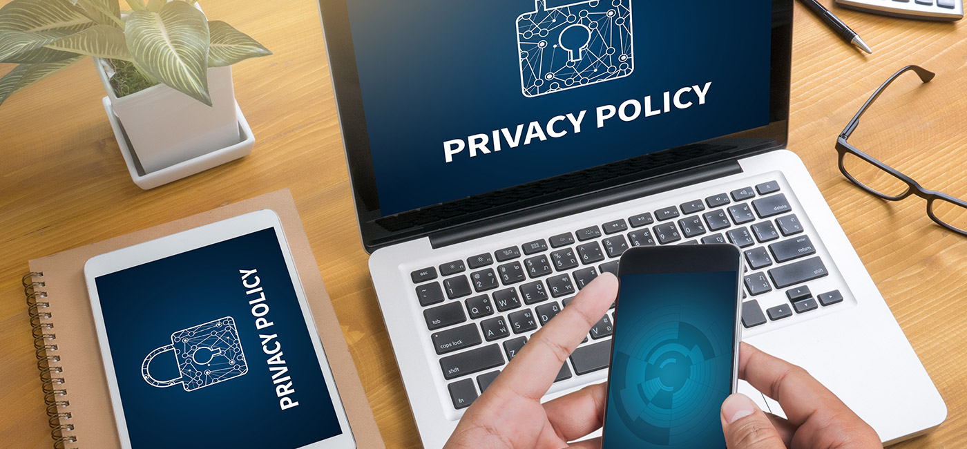 Privacy Policy Showing on a laptop screen person holding a cellphone eyeglasses on a desk plant on a desk ipad on desk